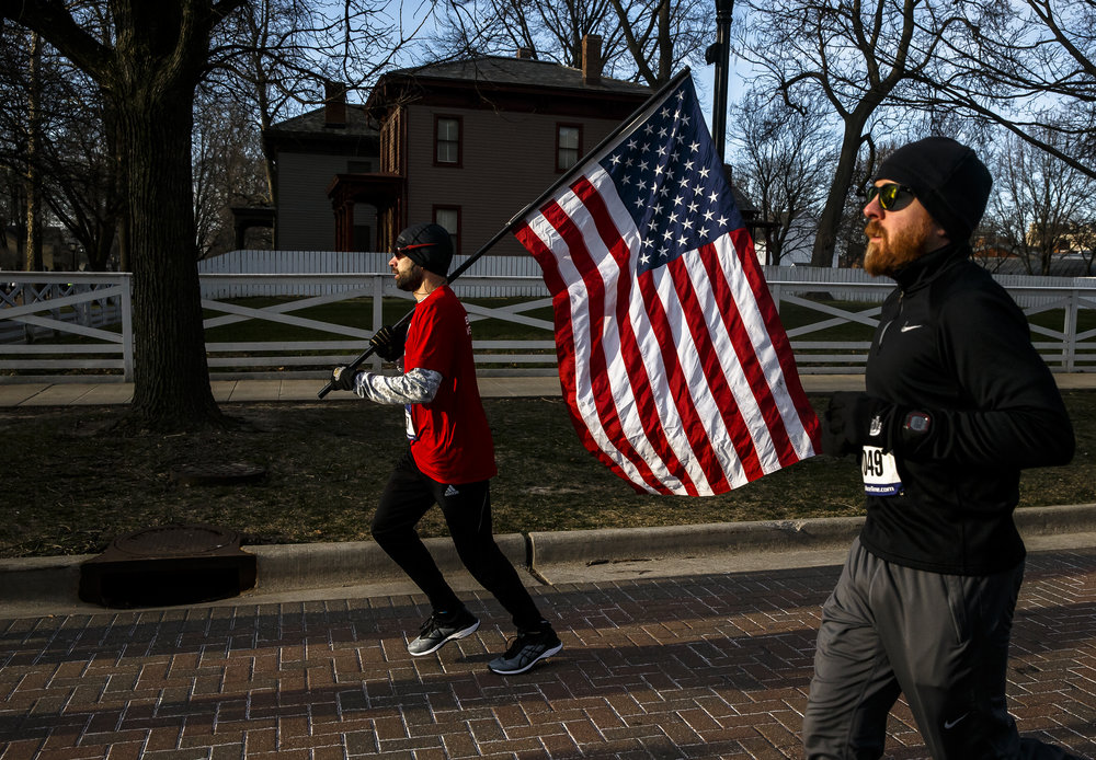 Tom Korth carries an American Flag as he heads towards the Lincoln Home on opening section of the 2018 Lincoln Presidential Half Marathon, Saturday, April 7, 2018, in Springfield, Ill. Korth ran the entire race with the flag finishing with a time of 1:59:04. [Justin L. Fowler/The State Journal-Register]