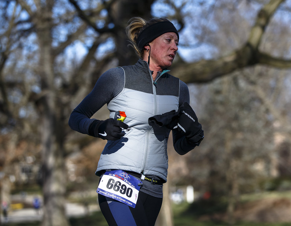 Teri Markley takes on some nutrition as she heads out of Washington Park up Lincoln Avenue during the 2018 Lincoln Presidential Half Marathon, Saturday, April 7, 2018, in Springfield, Ill. [Justin L. Fowler/The State Journal-Register]