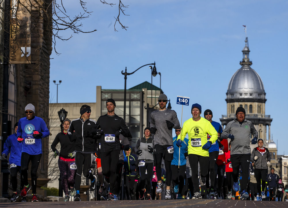 Pacer Bill Owens leads the group running at a pace of one hour and forty minutes as runners head east on Capitol Avenue towards the Lincoln Home during the 2018 Lincoln Presidential Half Marathon, Saturday, April 7, 2018, in Springfield, Ill. [Justin L. Fowler/The State Journal-Register]