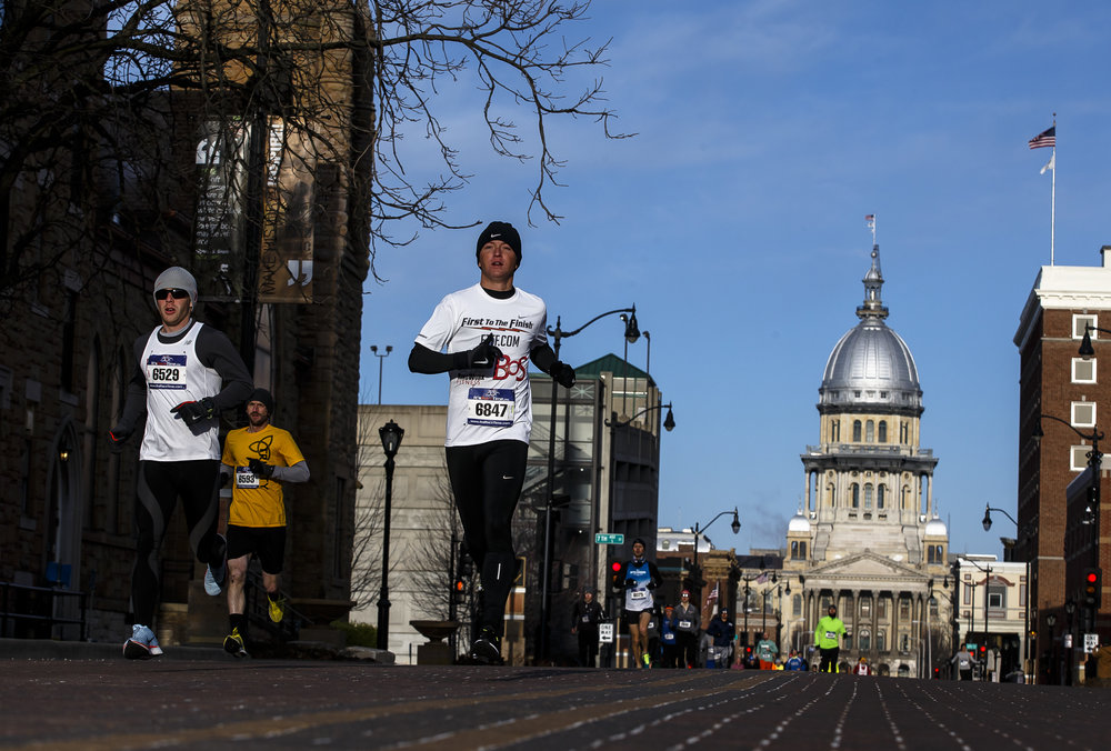Tyler Pence, center, heads out in the lead along with Henry Janssen, left, as they head east on Capital Avenue towards the Lincoln Home during the 2018 Lincoln Presidential Half Marathon, Saturday, April 7, 2018, in Springfield, Ill. Pence was the men's winner of the race with a time of 1:08:07. [Justin L. Fowler/The State Journal-Register]