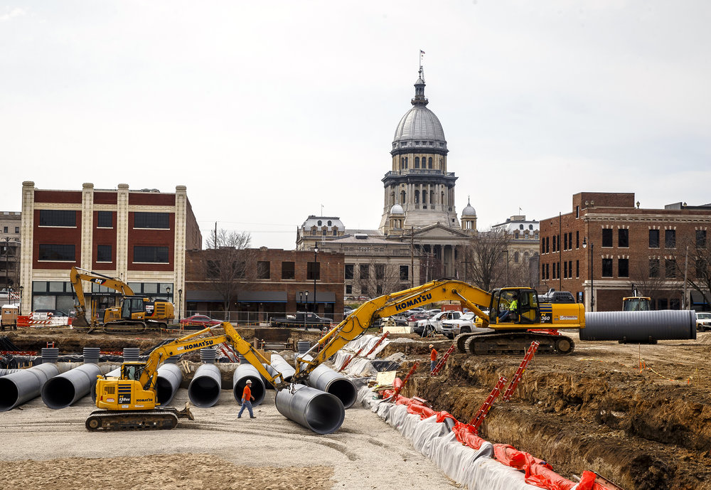 "Construction crews from O'Shea Builders work in a deep pit dug out from what was the former YWCA block as they install 60"" pipes that will create an underground water retention system, Friday, April 13, 2018, in Springfield, Ill. According to Matthew Allen, civil project manager estimator for O'Shea Builders, the system will be able to hold 350,000 gallons of water and is designed to help collect storm water and slow it down as it empties into the Town Branch sewer system. The system is one part of an overall plan to help alleviate downtown flooding and is slated to be completed by July. [Justin L. Fowler/The State Journal-Register]"