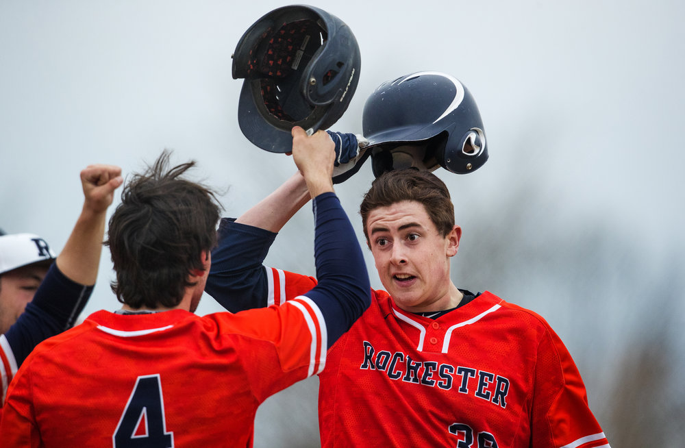 Rochester's Trace Miles tips his hat to his teammates as they welcome him to home base after his sixth inning walk-off homer against Springfield at Rochester High School Wednesday, April 11, 2018.  [Ted Schurter/The State Journal-Register]