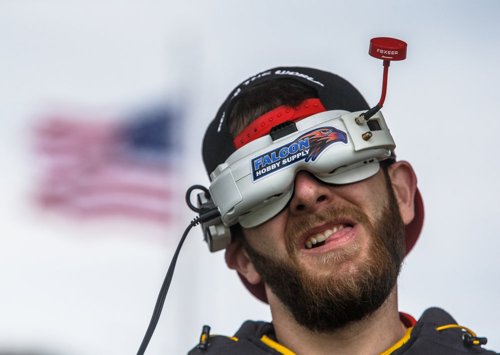 "Zach Carlson, center, shop manager of Falcon Hobby Supply and FPV pilot ""FalconX,"" watches the live feed of his drone through FPV (First Person View) goggles as he races in the pro division on the outdoor course at Falcon Hobby Supply, Sunday, April 22, 2018, in Springfield, Ill. The drones transmit a video signal that gives the pilots the view of what their drone sees as they race around an outdoor timed obstacle course with required gates they must pass through. [Justin L. Fowler/The State Journal-Register]"