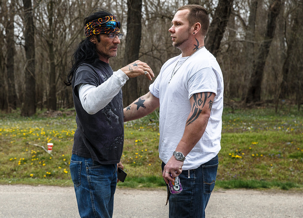 Micky Shomidie, left, the father of missing kayaker Shane Shomidie, gets a hug from Ronnie Beavers, right, who has been friends with Shane since they were kids, as family and friends wait along the Sangamon River as the recovery efforts continues near Riverside Park, Monday, April 23, 2018, in Springfield, Ill. [Justin L. Fowler/The State Journal-Register]