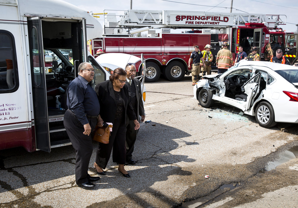 A woman who was a passenger in a van from Zion Baptist Church is helped to a car following an accident at Dirksen Parkway and Cook Street Tuesday, April 24, 2018 in Springfield, Ill. Four people on the bus, including the driver, and the driver of a white Nissan Altima were transported to the hospital. None of the injuries were life-threatening, according to the Springfield Fire Department. [Rich Saal/The State Journal-Register]