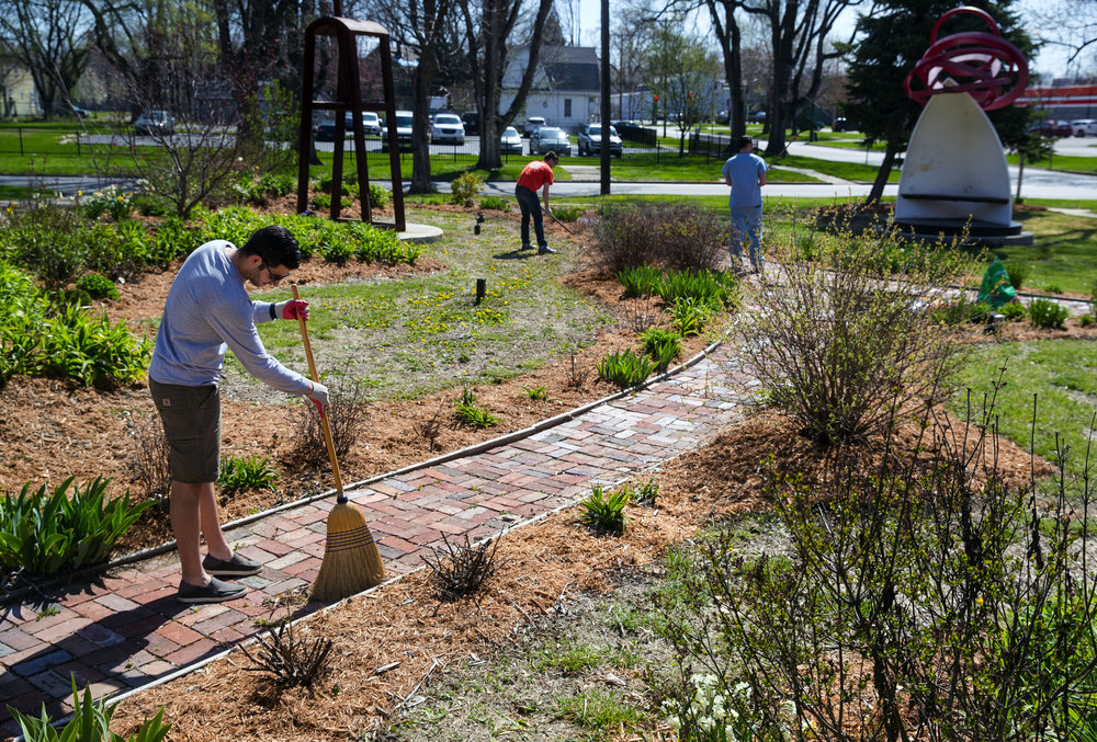 Southern Illinois University School of Medicine student Stephen Williams sweeps the pathways at the sculpture garden at the corner of 8th and Enos Avenue in Springfield during the school's  5th Annual Day of Service Thursday, April 26, 2018. [Ted Schurter/The State Journal-Register]