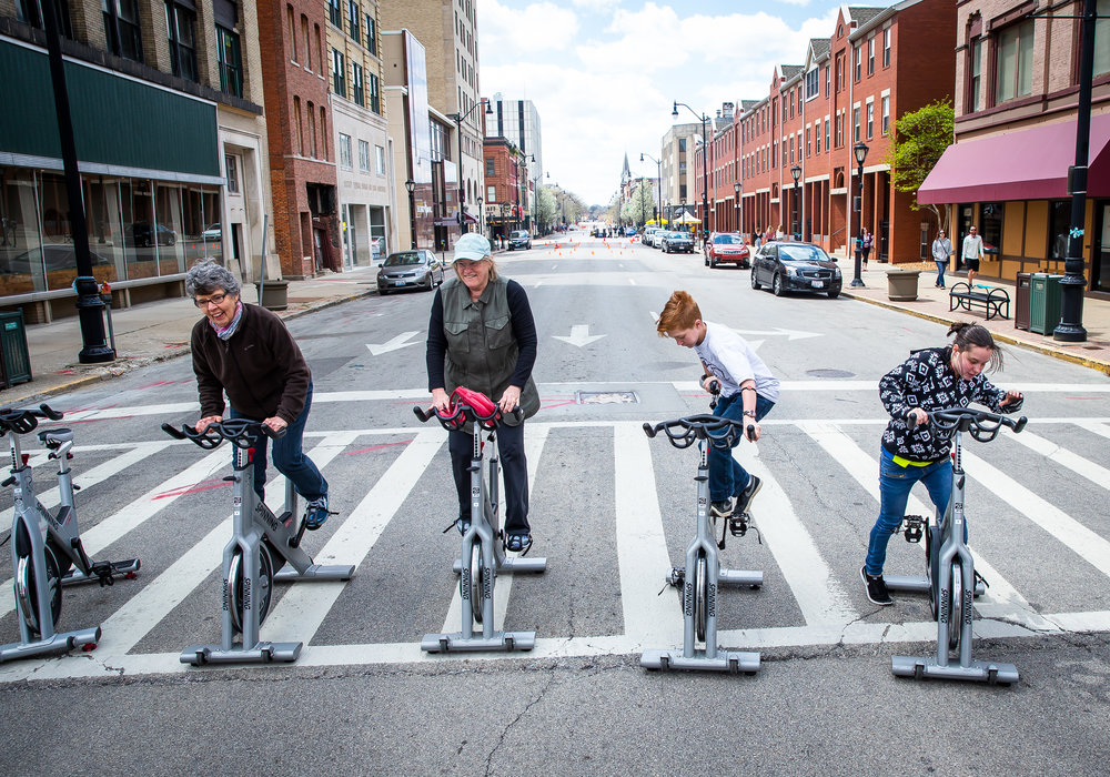 "Mary Thoele, left, Marilyn Cisco, Chandler Marquardt, 13, and Amy Thomas, 16, right, try out spin bikes during a demonstration of the YMCA spin class in the middle of a closed down Monroe Street during the Downtown Open Streets event, Saturday, April 28, 2018, in Springfield, Ill. Downtown Open Streets was an event put on by Downtown Springfield, Inc. and sponsored by Memorial Health System, and created a ""paved park"" by temporarily closing certain downtown streets and holding demonstrations promoting recreation and healthier living. [Justin L. Fowler/The State Journal-Register]"