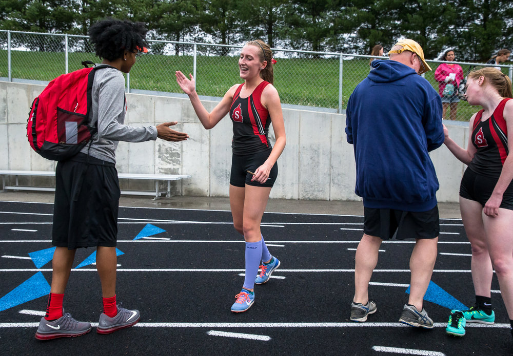 Springfield's Gabrielle Wood, center,  celebrates with Springfield girls track coach Kirby Hale, left, after winning the 3200m run setting a personal record with a time of 11:44.97 during the Girls CS8 Track & Field Meet at Eisenhower High School, Thursday, May 3, 2018, in Springfield, Ill. [Justin L. Fowler/The State Journal-Register]