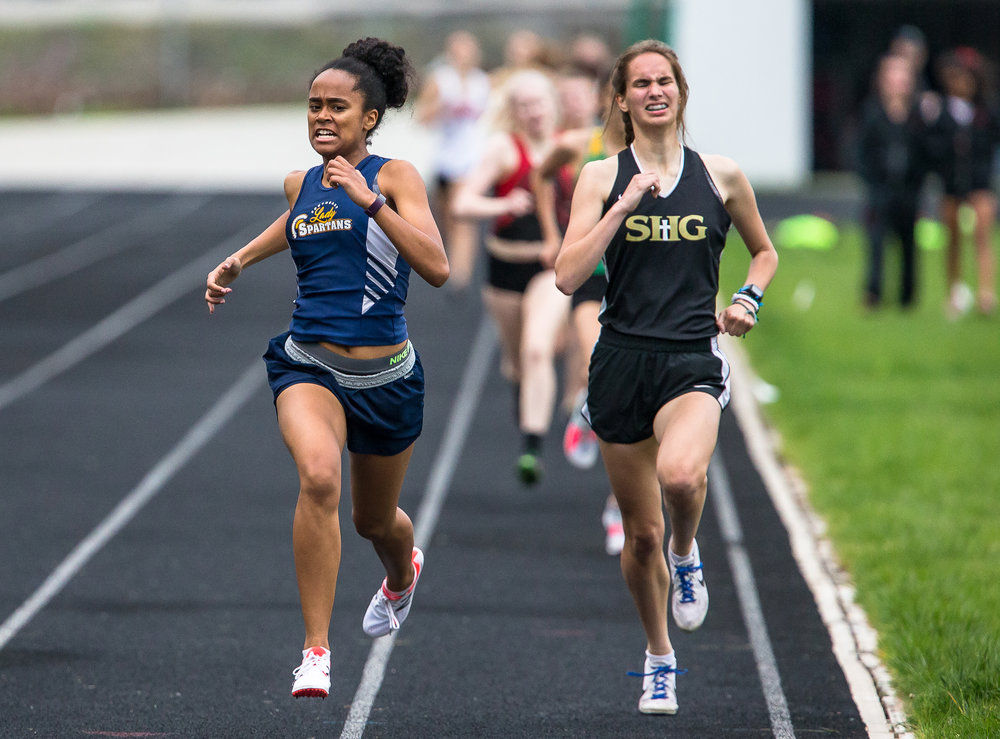 Southeast's Sydney Huffman, left, edges out Sacred Heart-Griffin's Mikayla Hady, right, to win the 800m run a set a new personal record with a time of 2:26.08 during the Girls CS8 Track & Field Meet at Eisenhower High School, Thursday, May 3, 2018, in Springfield, Ill. [Justin L. Fowler/The State Journal-Register]