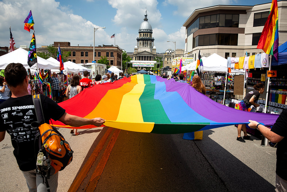 A rainbow flag carried by staff and volunteers from the Phoenix Center during the Springfield PrideFest parade, makes its way down Capitol Avenue Saturday, May 19, 2018 in Springfield, Ill. [Rich Saal/The State Journal-Register]