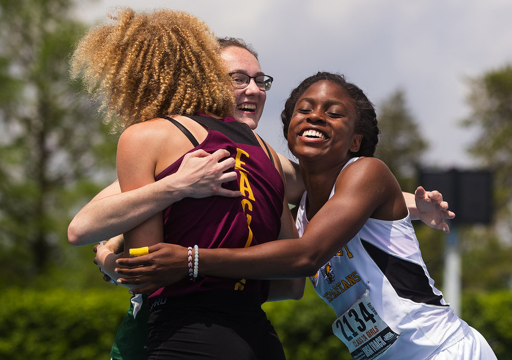 Southeast's Serena Bolden is embraced by Dunlap's Kiara Pauli and Geneseo's Erika Furbeck following Bolden's second place finish in the Class 2A 100 meter dash during the IHSA Track and Field State Finals at O'Brien Field in Charleston, Ill., Saturday, May 19, 2018.  [Ted Schurter/The State Journal-Register]