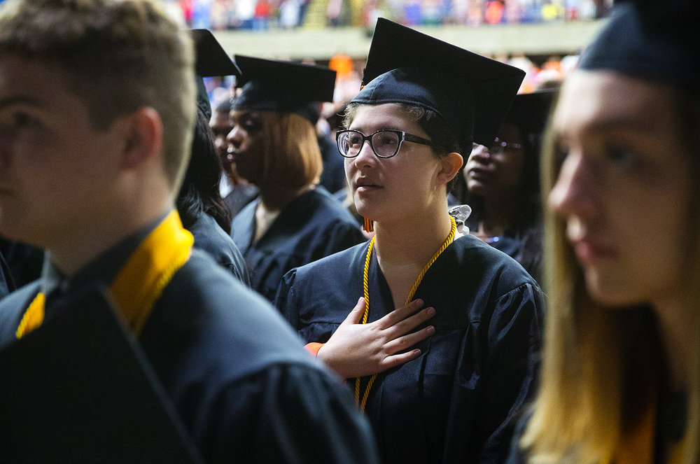 "Laura Betty places her hand on her heart during the playing of the ""Star Spangled Banner"" during the 99th Commencement for Lanphier High School at the Bank of Springfield Center Saturday, June 2, 2018. [Ted Schurter/The State Journal-Register]"