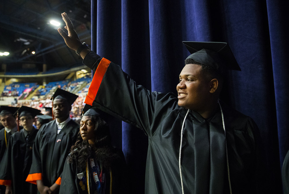 Christopher Ewing waves to the crowd as he waits to receive his diploma during the 99th Commencement for Lanphier High School at the Bank of Springfield Center Saturday, June 2, 2018. [Ted Schurter/The State Journal-Register]