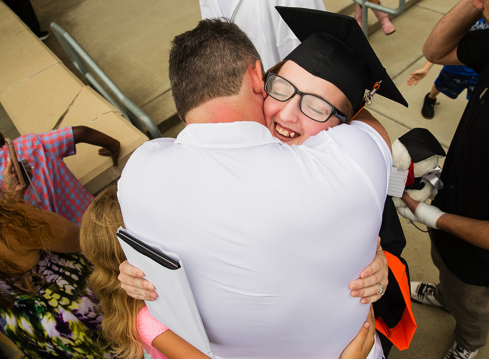 Jonathan Langley gives his daughter Bethanie a bear hug as he greets her after the 99th Commencement for Lanphier High School at the Bank of Springfield Center Saturday, June 2, 2018. [Ted Schurter/The State Journal-Register]