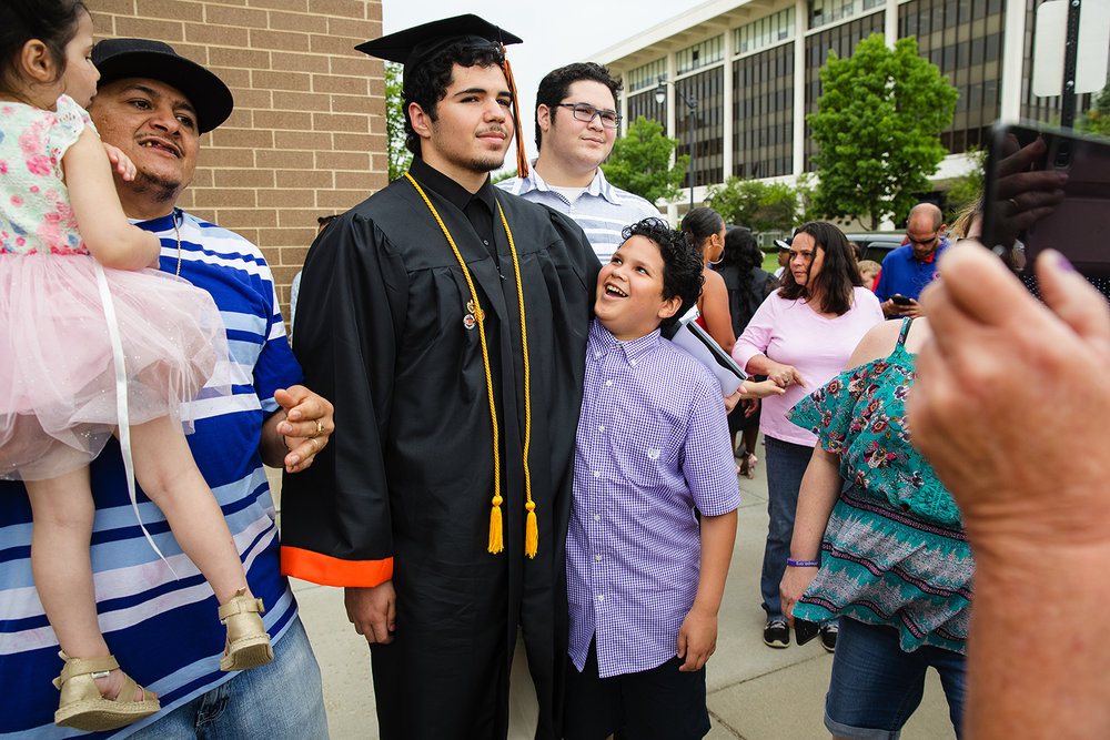 Brayan Reyes' little brother Noe looks up at him as he poses for photos with his dad Elmer and sister Katharine, left, and brother Juan, right, after the 99th Commencement for Lanphier High School at the Bank of Springfield Center Saturday, June 2, 2018. [Ted Schurter/The State Journal-Register]