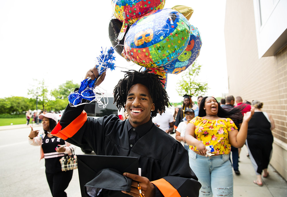 Mulik Williams carries a large bunch of celebratory balloons after the 99th Commencement for Lanphier High School at the Bank of Springfield Center Saturday, June 2, 2018. [Ted Schurter/The State Journal-Register]