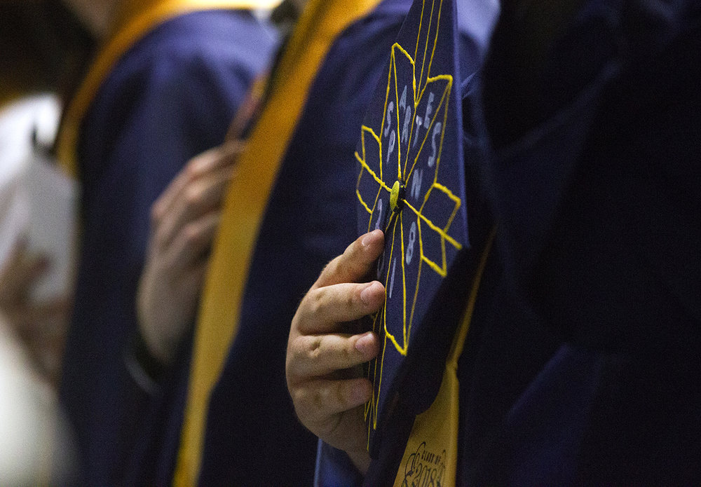A Southeast Spartan holds his cap over his heart during National Anthem at the 51st Commencement for Springfield Southeast High School at the Bank of Springfield Center Saturday, June 2, 2018. [Ted Schurter/The State Journal-Register]