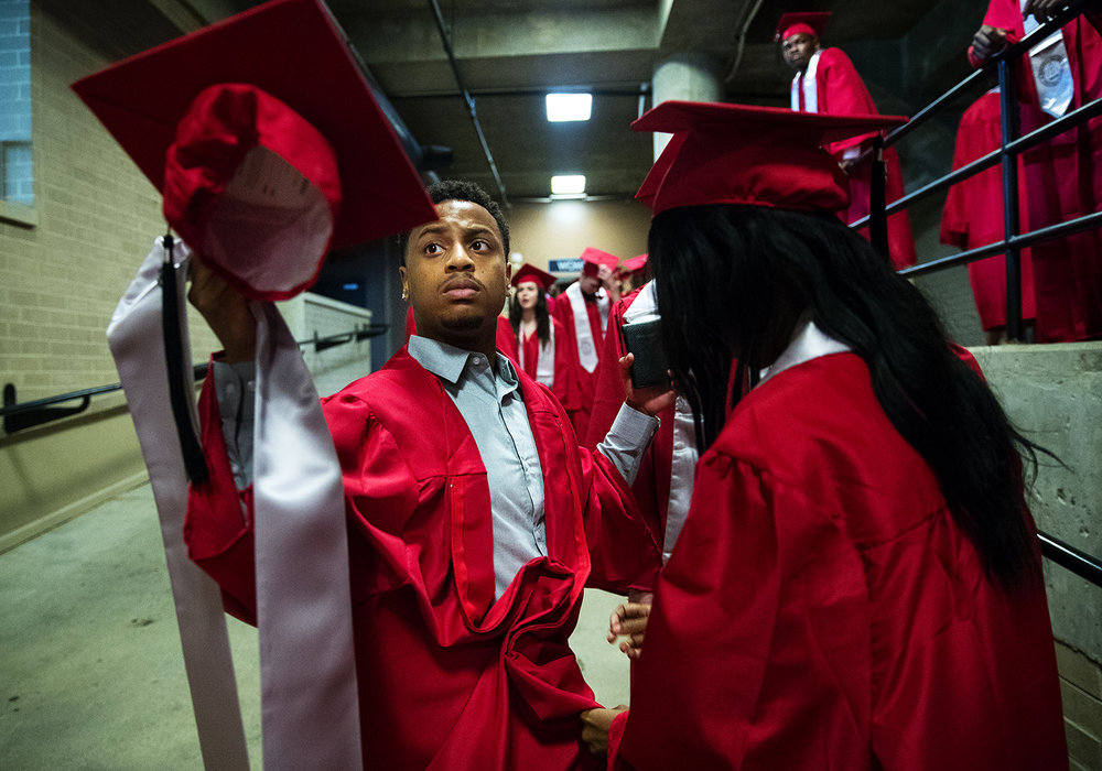 Miracle Shields helps D.J. Simmons into his gown before Commencement for Springfield High School at the Bank of Springfield Center Saturday, June 2, 2018. [Ted Schurter/The State Journal-Register]