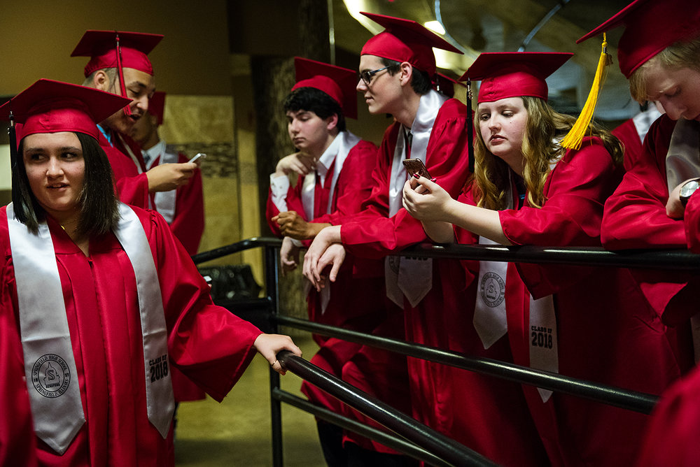 Hannah Vandeventer checks her phone as she waits with other students for Commencement for Springfield High School at the Bank of Springfield Center Saturday, June 2, 2018. [Ted Schurter/The State Journal-Register]