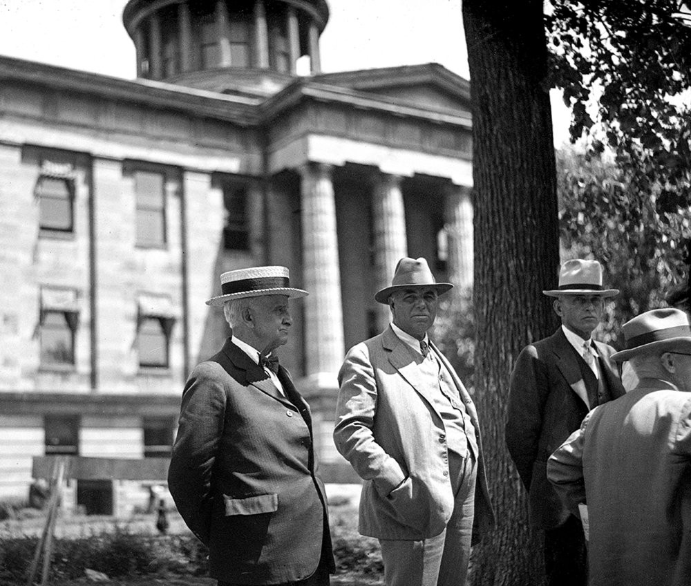Four men standing on lawn of Old State Capitol (courthouse). llinois State Register glass plate negative/Sangamon Valley Collection at Lincoln Library  C-98-904 negative # 1609
