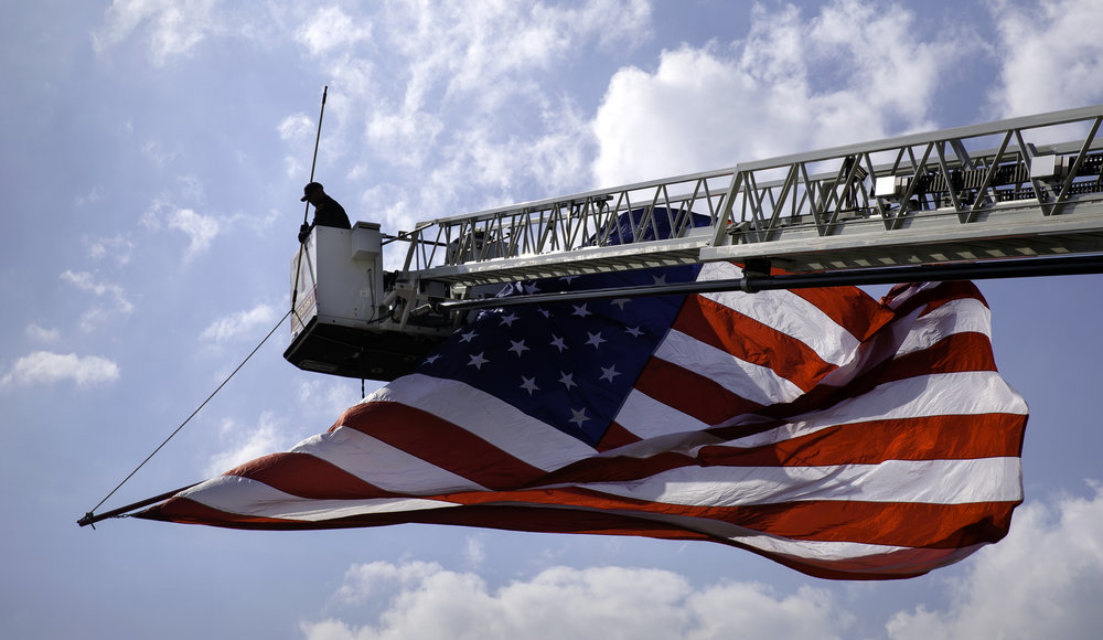 A member of the Springfield Fire Department wrangles a giant United States flag into place as it bellows above Monroe Street near the state capital Tuesday, May 1, 2018. The flag welcomed members of the Law Enforcement United bicycle ride that concluded at the Illinois Peace Officers Memorial. [Ted Schurter/The State Journal-Register]