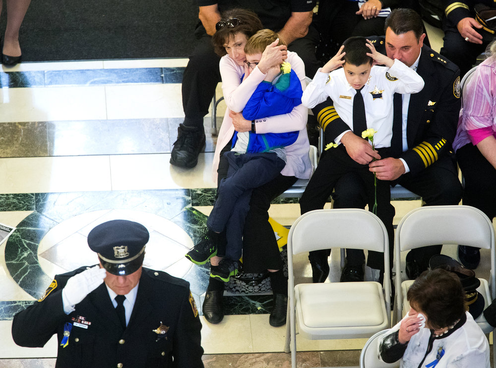 Dominic DePasquale sits in his dad Mario's lap and covers his ears before the Gun Salute during the Illinois Police Officers Memorial Ceremony at the Illinois State Library Thursday, May 3, 2018. DePasqaule is the Chief of Police for the Village of McCook. [Ted Schurter/The State Journal-Register]