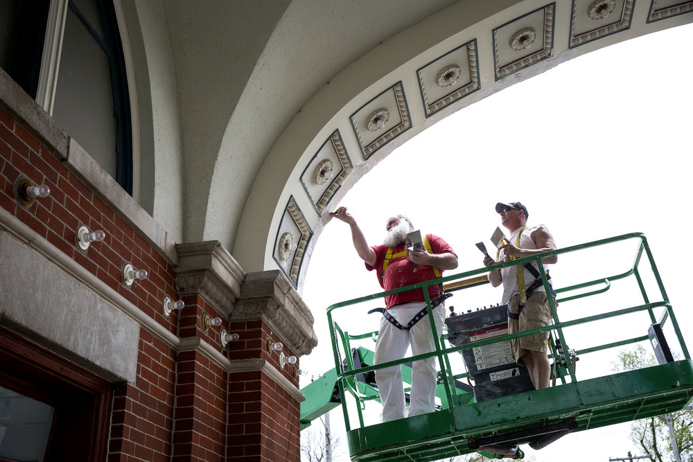 Dave Harris and Jason Cookson repair plaster on the historic Main Gate to the Illinois State Fairgrounds Friday, May 4, 2018 in Springfield, Ill. Painting the structure, which opened in 1910, will begin next week. [Rich Saal/The State Journal-Register]