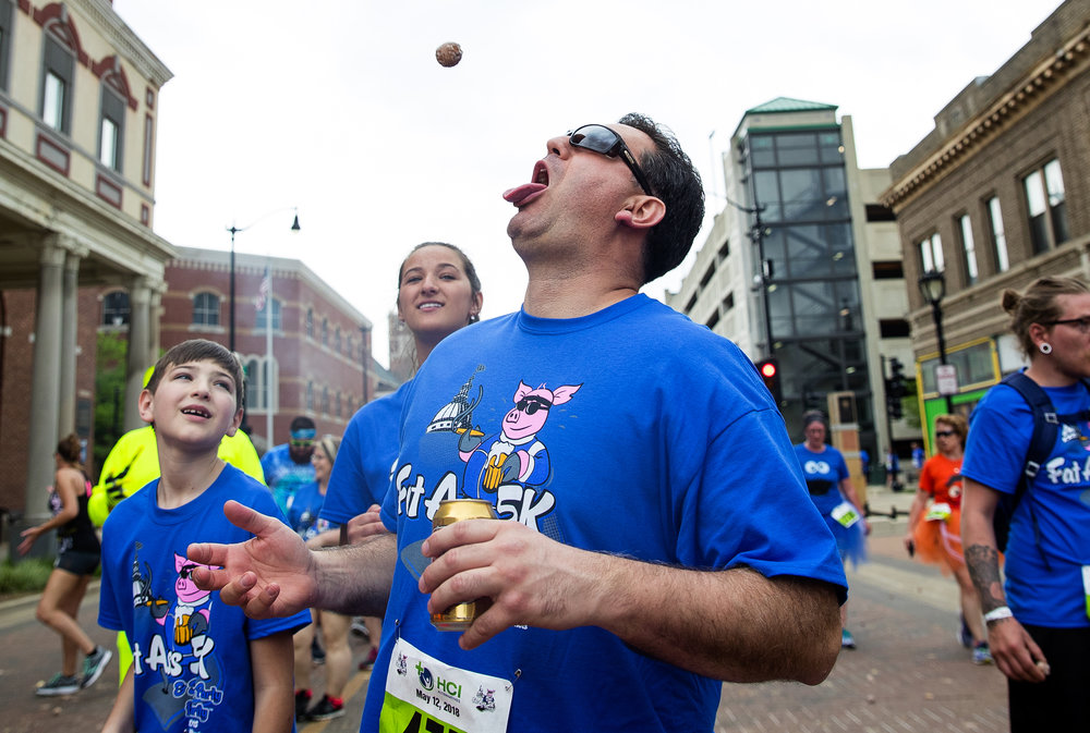 Ron Cole catches one of a flurry of flying donut holes during the Fat Ass 5K & Street Party for Charity in downtown Springfield Saturday, May 12, 2018. Cole estimates he caught about ten before moving down the course. [Ted Schurter/The State Journal-Register]
