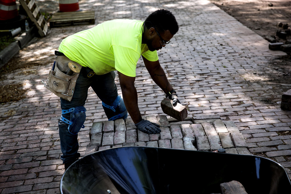 Antoine Harris stacks paver bricks removed from a portion of the 300 block of Cedar Street Thursday, May 17, 2018 in Springfield, Ill. The work is part of a program to maintain the historic character of the city's 13 miles of brick streets, according to Public Works Director Mark Mahoney. In the last three years the city has repaired about 4 miles of brick, and will do another mile this year at a cost of $500.000. Kinney Contractors, Inc. is doing the work. [Rich Saal/The State Journal-Register]