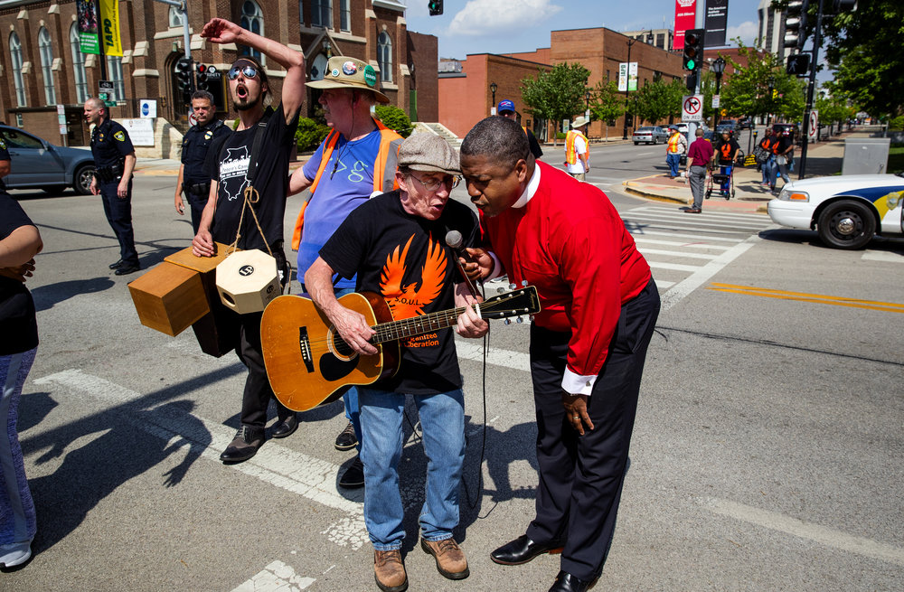 Tim Hickey, left, and Rev. Saeed Richardson, sing together as they leave the intersection of Second and Monroe Streets in Springfield, Il., Monday, May 14, 2018. The duo was joined by about 80 people, seven of whom temporarily blocked the intersection, who sang and chanted in protest in the name of the Poor People's Campaign. Today marks the first of what they say will be 40 days of nonviolent moral fusion direct action to fight poverty, systemic racism, militarism and ecological devastation. [Ted Schurter/The State Journal-Register]