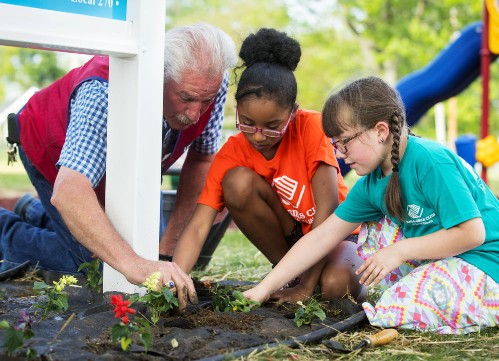 Ron Scattergood, an assistant store manager with Lowe's in Springfield, helps Kaliya Mckay Anastasia McFarland plant flowers around a new sign at the Boys & Girls Clubs of Central Illinois playground Thursday, May 17, 2018. The club received a $50,000 makeover from Lowe's  that included the playground, some landscaping, new signage, and all new HVAC thermostats inside the facility. [Ted Schurter/The State Journal-Register]