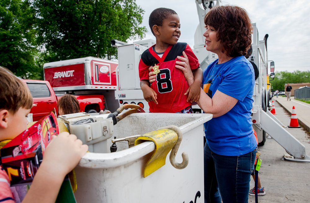 Meg Justison, an Early Start Teacher at the Early Learning Center, hoists up one of her students, Prince, 4, to help him see inside the bucket the linemen use to access power lines from City, Water, Light and Power on display during Big Truck Day at the Early Learning Center, Friday, May 18, 2018, in Springfield, Ill. Youngsters from around the are had the opportunity to explore heavy equipment from a firetruck and ambulance to a delivery vehicle from the USPS. [Justin L. Fowler/The State Journal-Register]