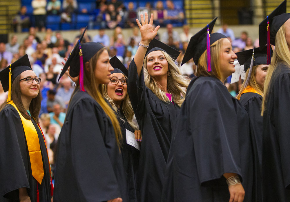 Students wave to the crowd as they process in during  commencement exercises for Lincoln Land Community College at the Bank of Springfield Center Friday, May 18, 2018. The school conferred more than 2,000 certificates and degrees during the ceremony. [Ted Schurter/The State Journal-Register]