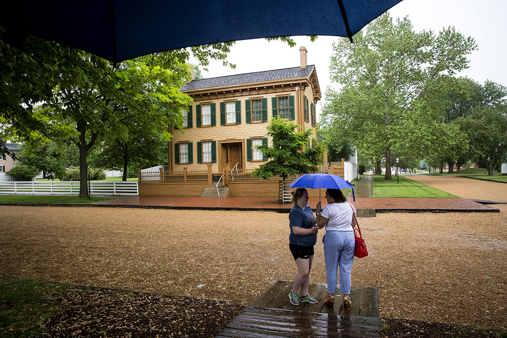 Gov. Bruce Rauner's office announced record tourism numbers in 2017 for the state, reporting an increase of 1.6 million travelers, an increase of 3 percent over the previous year. At the Lincoln Home Tuesday, May 15, 2018, Jillian Batty, left, and Alexandria Castellanos waited in a light rain for their turn to see the home. [Rich Saal/The State Journal-Register]