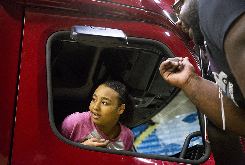 "Myia Anderson, a freshman at Southeast High School, listens to Malcolm Groves explain what the driver of a semi-truck can, and cannot see during ""Teens, Trucks and Traffic"" hosted by the Illinois Trucking Association Tuesday, May 15, 2018 at the Bank of Springfield Center in Springfield, Ill. The first-time event in Springfield offered 360 drivers education students from the three city high schools and Chatham Glenwood the opportunity to sit in a truck and learn about the blind spots, or no-zones, around a semi. [Rich Saal/The State Journal-Register]"