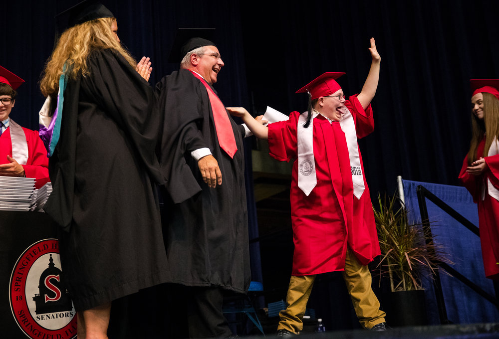 Garret Chambers waves to the crowd as he crosses the stage during Commencement for Springfield High School at the Bank of Springfield Center Saturday, June 2, 2018. [Ted Schurter/The State Journal-Register]