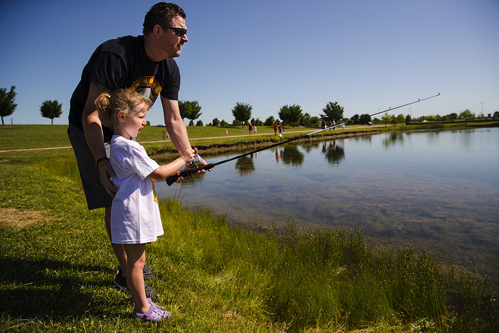 Doug Matthew helps his four-year-old daughter Paige reel in her line during a Cops and Bobbers Fishing Clinic at Southwind Park Sunday, June 3, 2018. The Springfield Police Department has hosted the free family event and provided equipment, refreshments and instruction for three years. [Ted Schurter/The State Journal-Register]