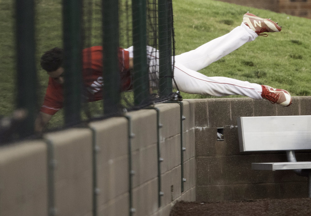 Glenwood's Jalen Ping dives over the wall as he tries to run down a Troy Triad foul ball during the class 3A Baseball Super Sectional at GCS Ballpark  in Sauget, Ill., Monday, June 4, 2018. [Ted Schurter/The State Journal-Register]
