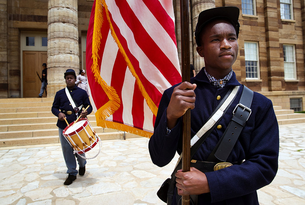 Shawntraree Lucas carries a U.S. flag down the steps of the Old State Capitol as he and other members of the Spirit of Lincoln Youth Leadership Academy prepare for the Civil War Camp Flag Raising Ceremony Friday, June 8, 2018. The group portrays soldiers in the  29th Regiment, United States Colored Infantry and also women from the Freedman's Lady's Aid Society and is a part of the History Comes Alive program that features storytelling and interaction from live history presenters in full period dress. The program hosts recurring events six days a week at various historic sites around Springfield. [Ted Schurter/The State Journal-Register]