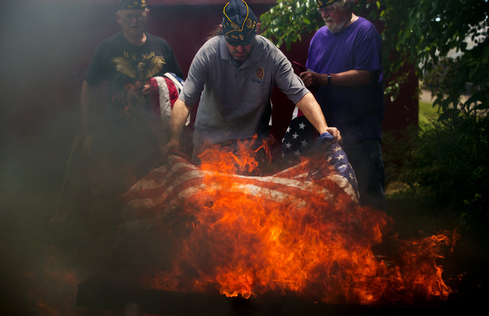 Michael Bunner adds a U.S. flag to the fire during a flag disposal ceremony hosted by American Legion Post 263 and the Lincoln Chapter of the Daughters of the American Revolution Thursday, June 14, 2018. The Post collects flags throughout the year to dispose of during the ceremony. Thursday was also Flag Day and commemorates the 1777 resolution by the Continental Congress calling for the creation of the United States flag. [Ted Schurter/The State Journal-Register]