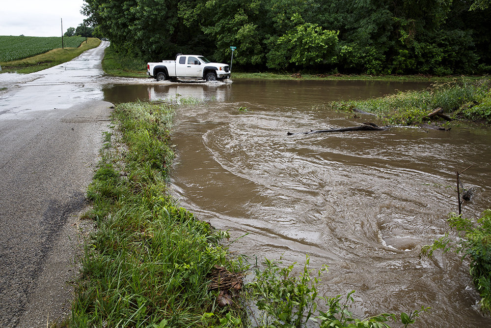 Water from a timbered area at County Roads 625 East and 2150 North in Christian County overwhelms drainage pipe under the roadway and floods the intersection after heavy rain overnight Monday, June11, 2018 near Edinburg, Ill. [Rich Saal/The State Journal-Register]