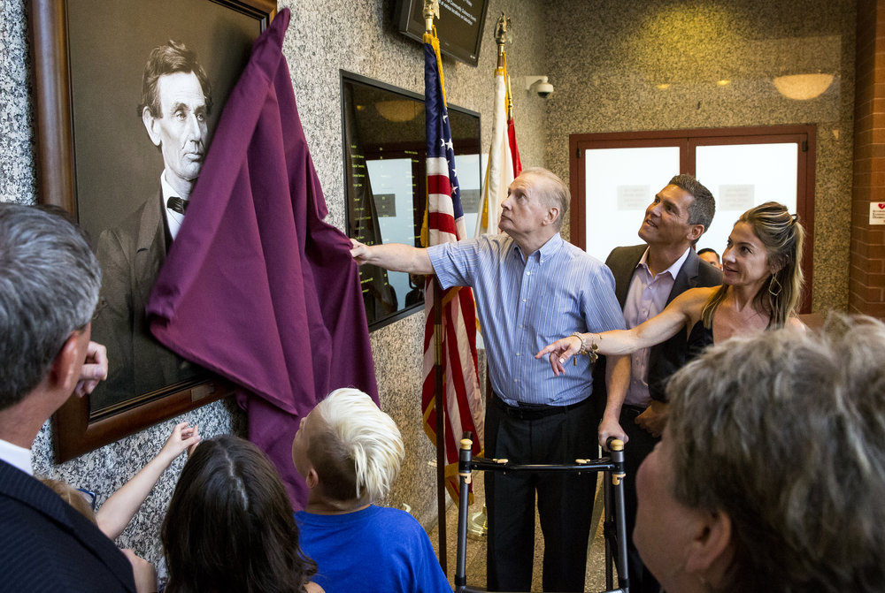 """Former Illinois Attorney General Jim Ryan, accompanied by his family including his son Matt and daughter Amy, unveils a photographic print of Abraham Lincoln made in 1860 during a ceremony Wednesday, June13, 2018 in the lobby of the Sangamon County Courthouse in Springfield, Ill. The print was donated by Dr. & Mrs. Peter Doris in honor of Ryan, who served from 1995 to 2003 under Governors Jim Edgar and George Ryan. The famous image of the then Republican candidate for president was made by Chicago photographer Alexander Hessler for the campaign during a session at the Old State Capitol. Lincoln said later the photo Òlooks better and expresses me better than any I have ever seen."""" The Illinois State Historical Society, which owns the image, has sought sponsors to place the photograph in each of Illinois' 102 county courthouses in time for the upcoming bicentennial celebration. [Rich Saal/The State Journal-Register]"""