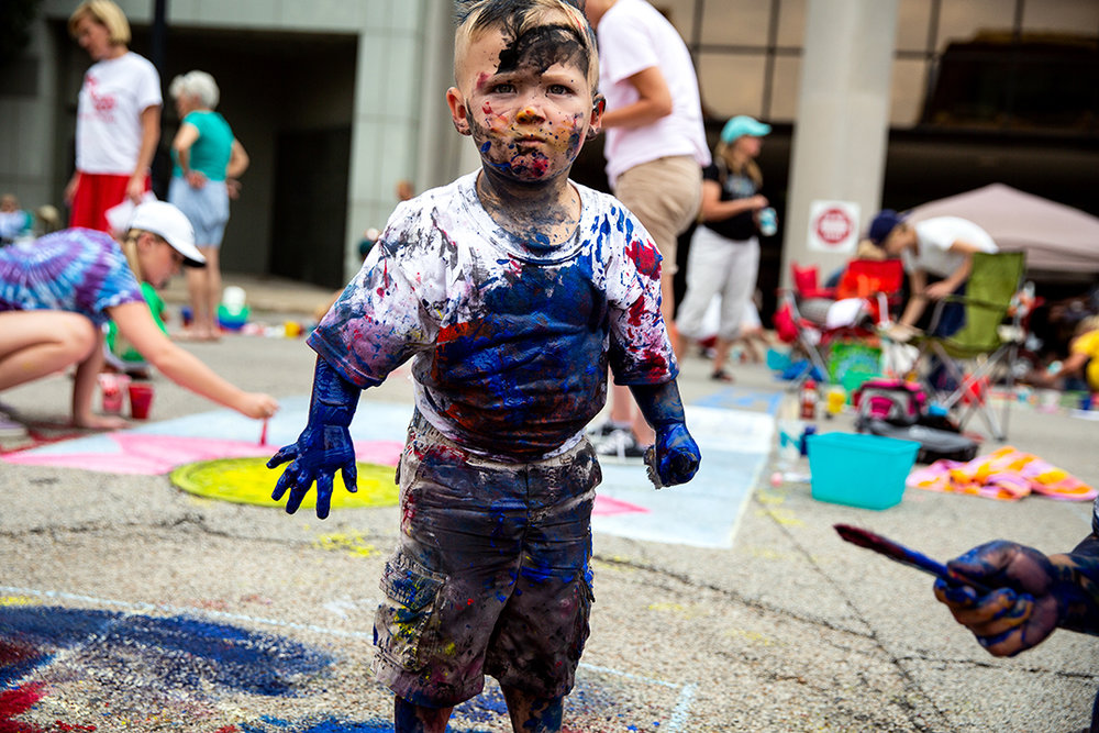 Josiah Guzoukis, 2, painted the street a little and himself a lot while with his mother Christy Painter at the 2018 Paint the Street festival hosted by the Springfield Art Association Saturday, June 23, 2018 on Washington Street in Springfield, Ill. [Rich Saal/The State Journal-Register]