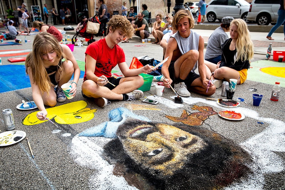 """Lili Beard, left, Alex Rothschild and Jonathan Johnson work together on a portrait of Bob Ross, the late artist and host of the public television program, """"The Joy of Painting,"""" at the 2018 Paint the Street festival hosted by the Springfield Art Association Saturday, June 23, 2018 on Washington Street in Springfield, Ill. [Rich Saal/The State Journal-Register]"""