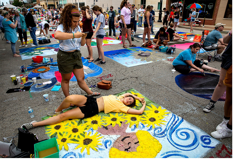 Isabella Lang snaps a photo of her friend, Natalie Lutz lying on their portrait of a girl in sunflowers during the 2018 Paint the Street festival hosted by the Springfield Art Association Saturday, June 23, 2018 on Washington Street in Springfield, Ill. [Rich Saal/The State Journal-Register]