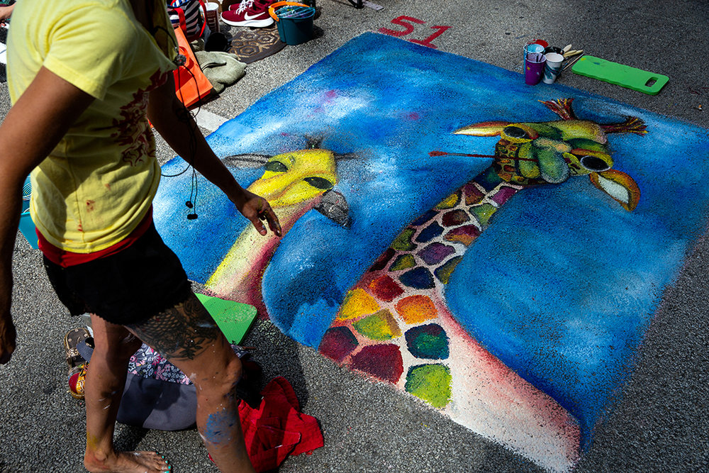 Kelly Smith inspects her painting of two giraffes, one painting a portrait of the other, during the 2018 Paint the Street festival hosted by the Springfield Art Association Saturday, June 23, 2018 on Washington Street in Springfield, Ill. [Rich Saal/The State Journal-Register]