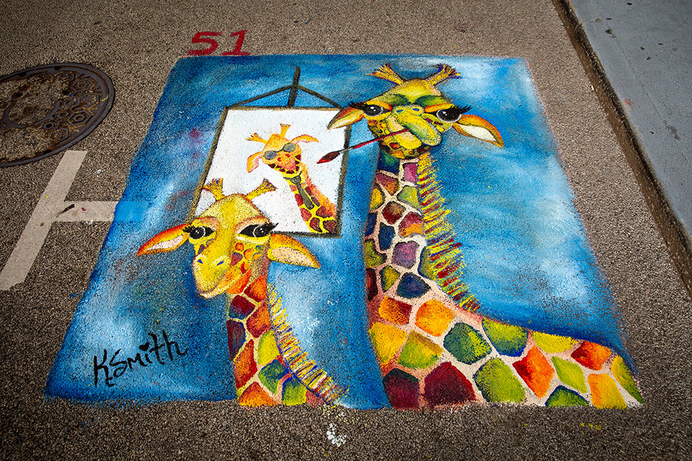 Kelly Smith's painting of two giraffes, one painting a portrait of the other at the 2018 Paint the Street festival hosted by the Springfield Art Association Monday, June 18, 2018 on Washington Street in Springfield, Ill. [Rich Saal/The State Journal-Register]