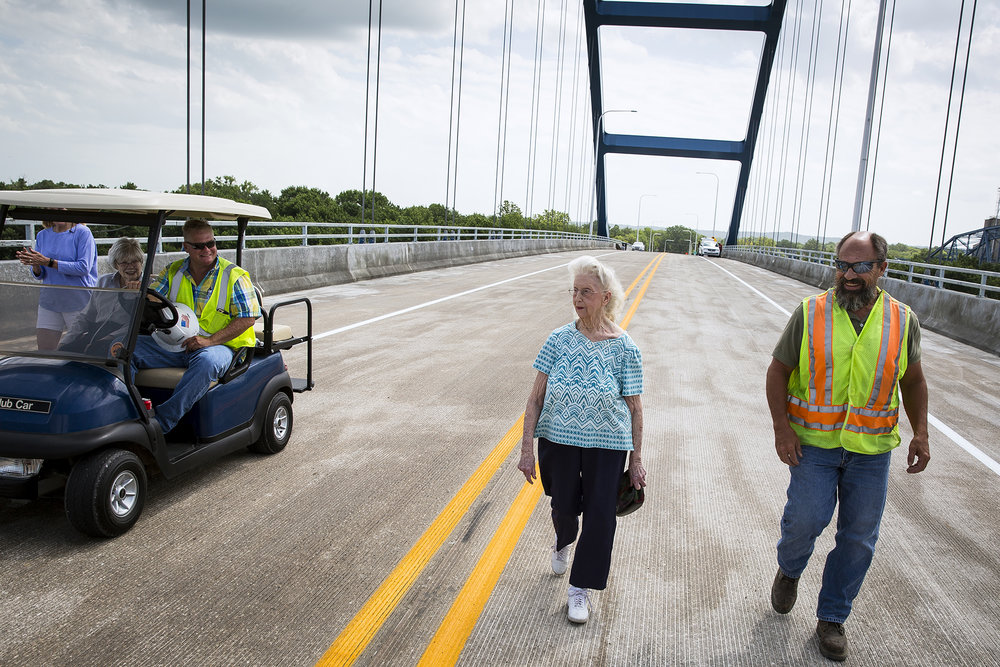 Delores Evans, 94, walks across the top of the new Illinois 104 bridge over the Illinois River at Meredosia two hours before it was officially opened Tuesday, June19, 2018 in Meredosia, Ill. Evans' home in Meredosia is just a few feet from the approach to the bridge and the offer to see it first hand came from Scott Halverson, left, of Halverson Construction, who says Evans put up with a lot during construction. Halverson's mother, Mary, rode with him in the golf cart. At right is Ron Archambeau, District 6 construction engineer for the Illinois Department of Transportation. [Rich Saal/The State Journal-Register]
