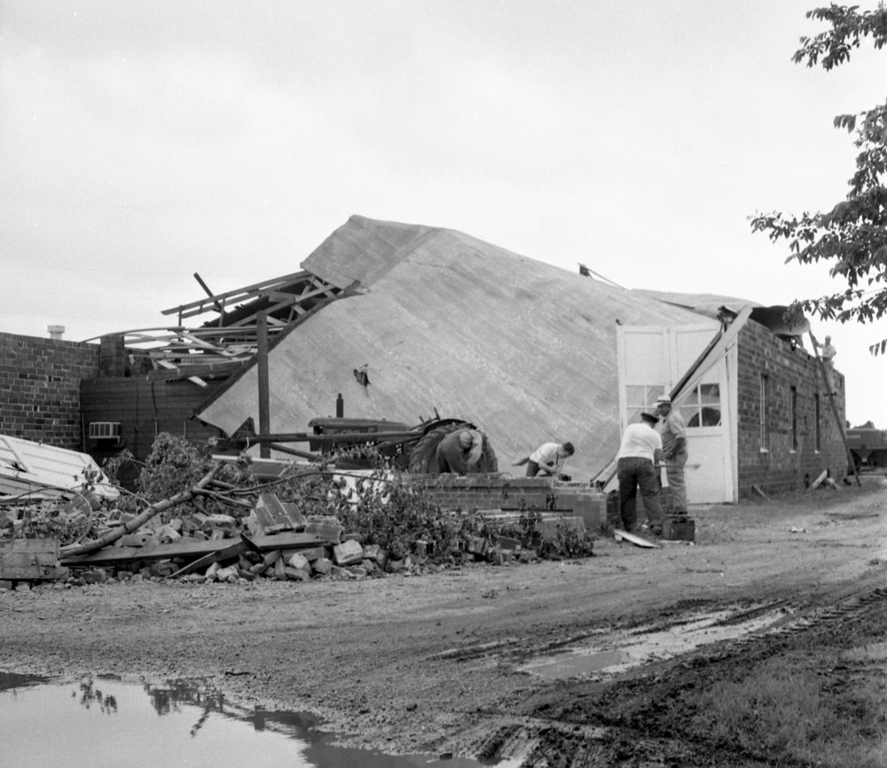 Workmen clean up damage to the Blakely Implement Co. on Wabash Avenue June 15, 1957, the day after a tornado struck Springfield. The storm caused more than $1 million in damages, killed three people, injured more than 50 and destroyed 20 to 25 homes. File/The State Journal-Register