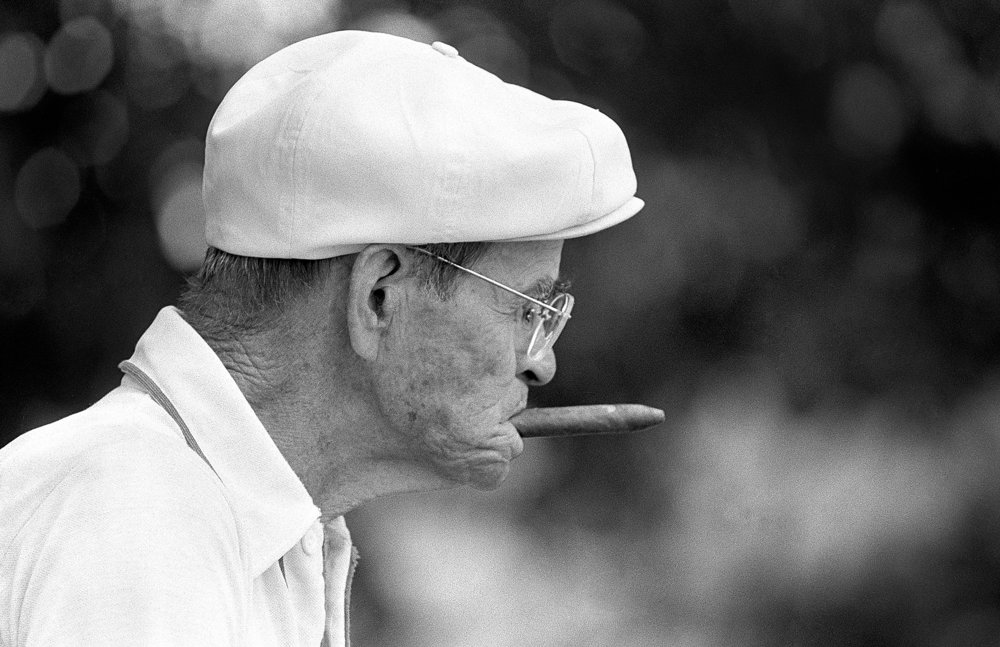"George Kurniskie, 81, chews a cigar while watching friend play shuffleboard in Lincoln Park Thursday, July 18, 1985. ""I'm the chief kibitzer,"" Kurniskie said, ""I used to be pretty good, but I can't cut the mustard anymore. Now, I help call the close shots.""  Greg Mellis/The State Journal-Register"
